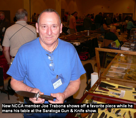 New NCCA member Joe Trabona shows off a favorite piece while he mans his table at the Saratoga Gun & Knife show.