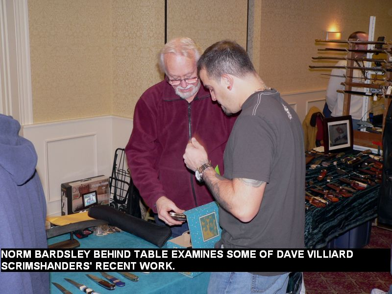 Norm Bardsley behind table examines some of Dave Villiard Scrimshanders' recent work.